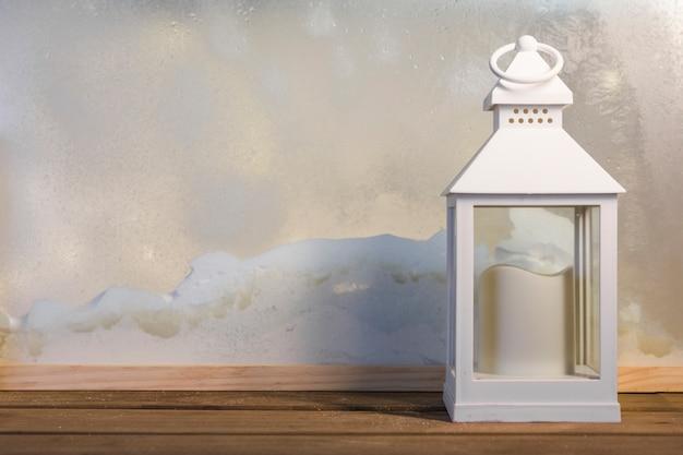 Lanterne avec bougie sur planche de bois près de tas de neige par la fenêtre Photo gratuit