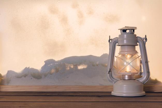 Lanterne à gaz sur une planche de bois près de tas de neige par la fenêtre Photo gratuit