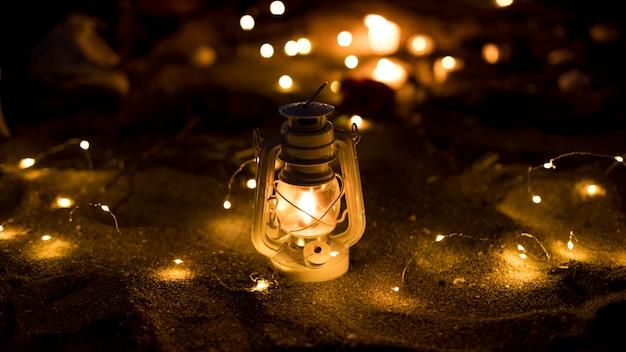 Lanterne Avec Guirlande Allumée Sur Le Sable Photo gratuit