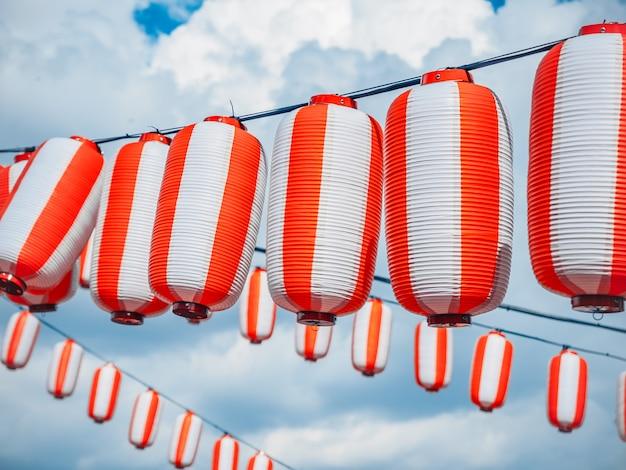 Lanternes japonaises en papier rouge-blanc chochin suspendues sur ciel bleu nuageux Photo Premium