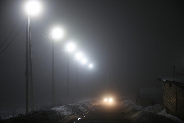 Lanternes le long de la route de nuit dans le brouillard Photo Premium