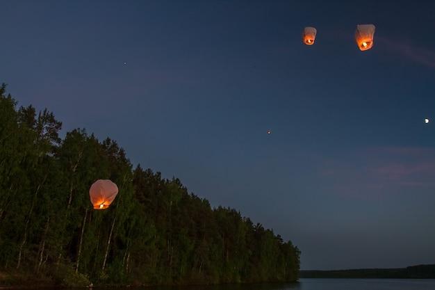 Lanternes volantes chinoises, survolant le lac dans l'obscurité Photo Premium