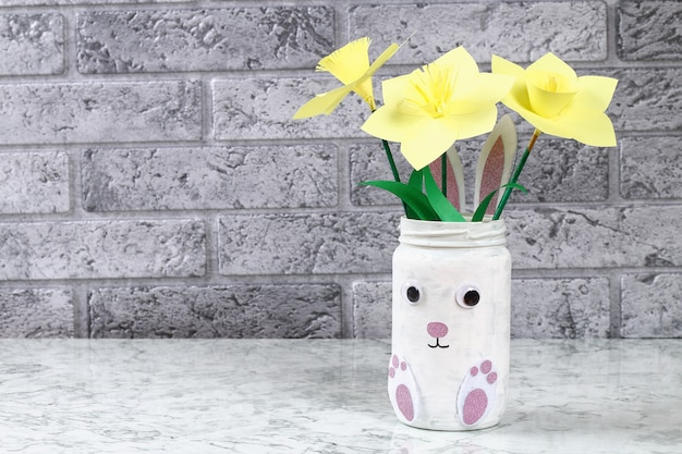 Lapin de bricolage vase de pâques de bocal en verre, feutre, yeux écarquillés sur fond vert Photo Premium