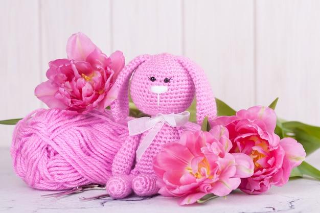 Lapin rose avec des tulipes. décor saint valentin. jouet tricoté, amigurumi, créativité Photo Premium