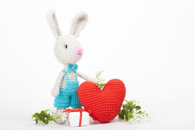 Lapin tricoté avec un coeur. décor saint valentin. jouet tricoté, amigurumi, carte de voeux. Photo Premium
