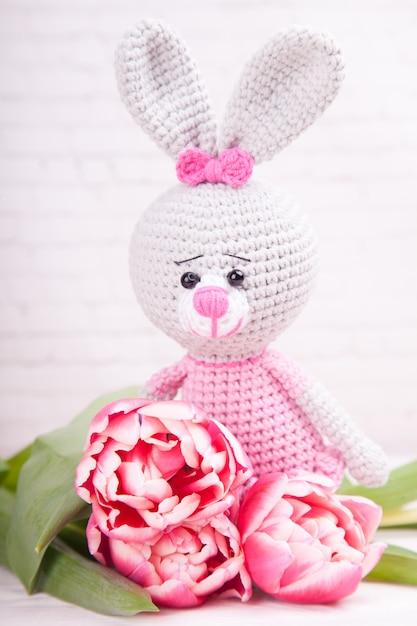 Lapin tricoté. décor de fête. tulipes roses délicates. la saint valentin. jouet tricoté à la main, amigurumi Photo Premium