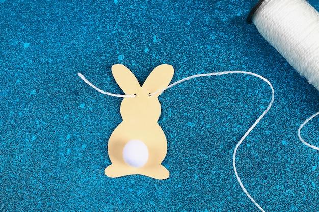 Les lapins de guirlande de pâques bricolage fait fond de papier bleu. Photo Premium