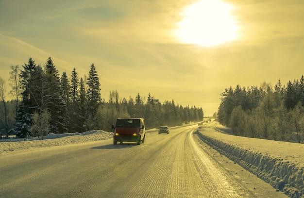 Laponie Finlandaise. Route Forestière D'hiver Et Soleil. Voitures Et Bus Photo Premium