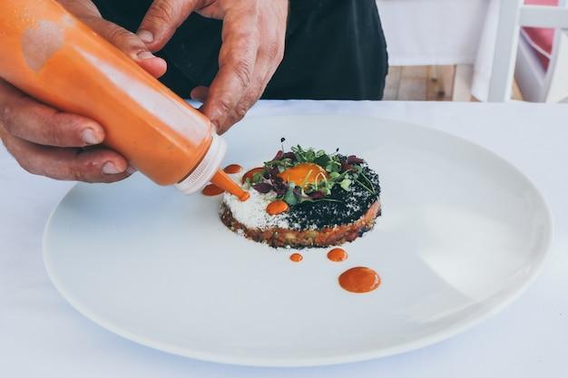 Large Gros Plan D'une Personne Versant Du Ketchup Sur Un Repas Cuit Sur Une Plaque Blanche Photo gratuit