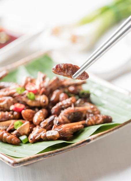 Larve frite sur des baguettes, manger des insectes comestibles et de la nourriture locale en thaïlande Photo Premium