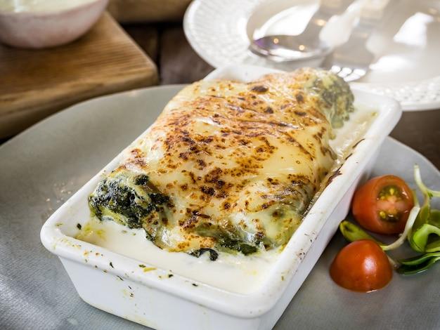 Lasagne en cocotte en céramique servie avec tomate et fines herbes, cuisine italienne Photo Premium