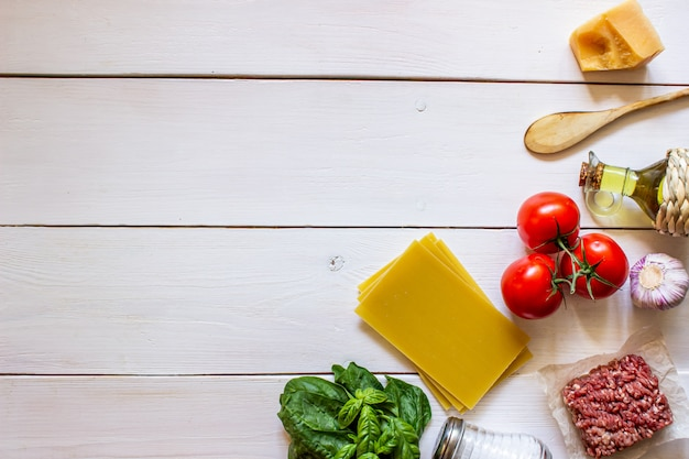 Lasagnes, Tomates, Viande Hachée Et Autres Ingrédients. Fond En Bois Blanc Cuisine Italienne. Photo Premium