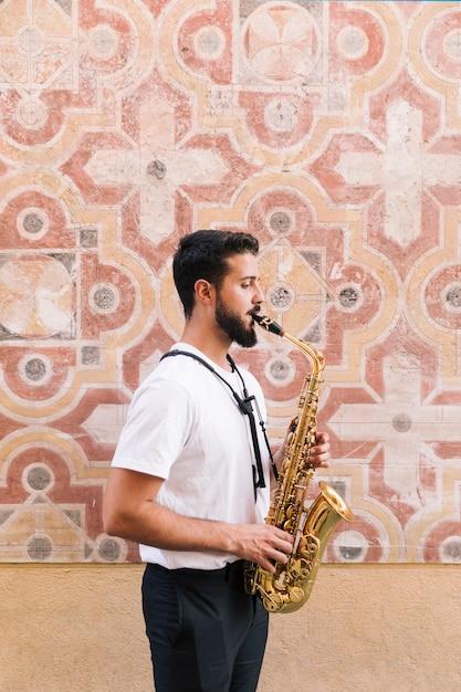 Latéral, homme, coup moyen, jouer, saxophone, à, géométrique, fond Photo gratuit