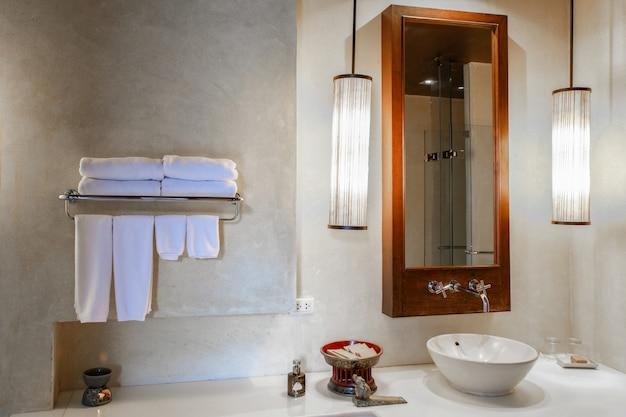 Lavabo en marbre moderne dans les toilettes ou la salle de bains d'un hôtel avec articles de toilette et serviettes propres Photo Premium