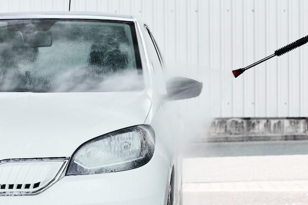 Lavage D'une Automobile électrique Blanche Dans De L'eau à Haute Pression Au Lavage De Voiture Manuel. Concept De Service De Nettoyage Photo Premium