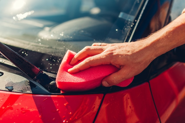 Lavage de voitures. homme, voiture de nettoyage avec une éponge savonneuse à l'extérieur. fermer Photo Premium