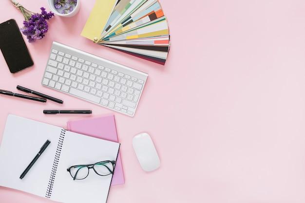 Lavande; téléphone portable; clavier et souris avec papeterie de bureau sur fond rose coloré Photo gratuit