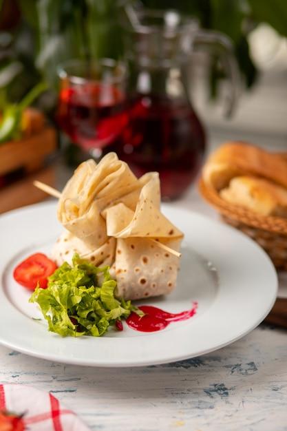 Lavash Fourré Et Fourré à La Salade De Tomates Et De Laitue Dans Une Assiette Blanche Photo gratuit