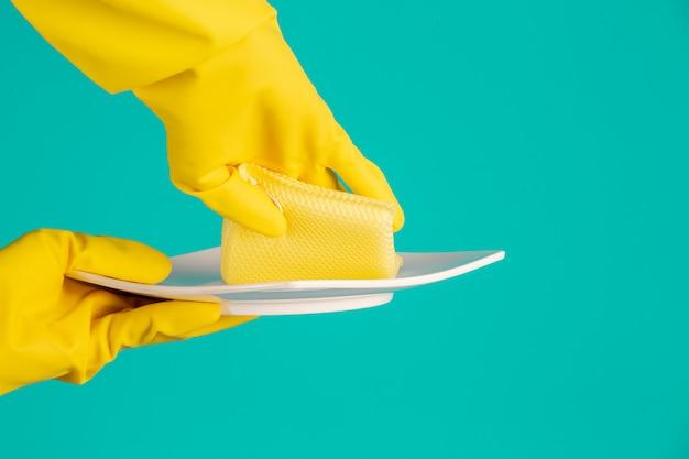 Lave-vaisselle portant des gants jaunes sur un bleu. Photo gratuit