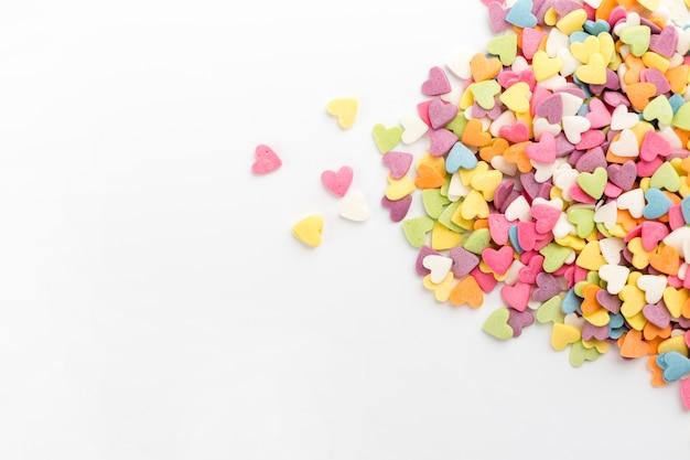 Lay plat de bonbons colorés en forme de coeur Photo gratuit