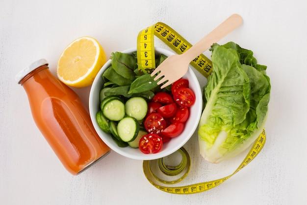 Lay plat de bouteille de salade et de jus Photo gratuit