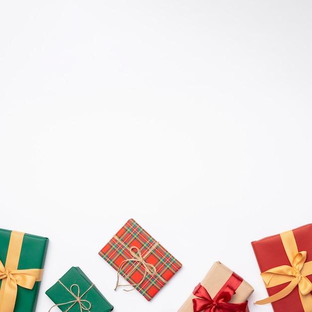 Lay plat de cadeaux de noël sur fond blanc avec espace de copie Photo gratuit