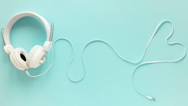 Lay plat d'écouteurs sur fond uni Photo gratuit