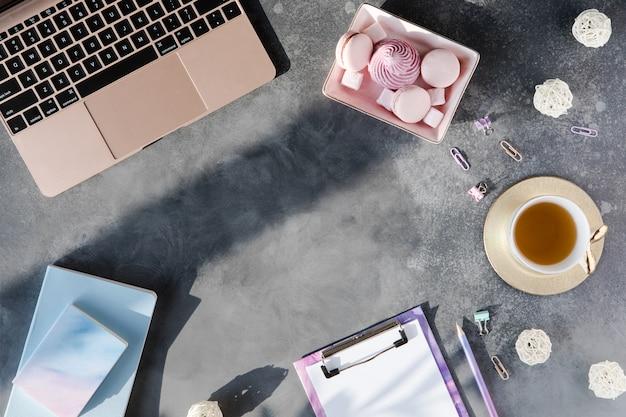 Lay plat de papeterie de bureau avec une tasse de thé avec guimauve et ordinateur portable sur un fond gris avec des ombres. Photo Premium