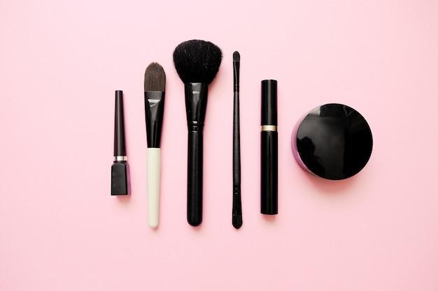 Lay plat de produits de maquillage de mode féminine sur fond de couleur pastel Photo Premium