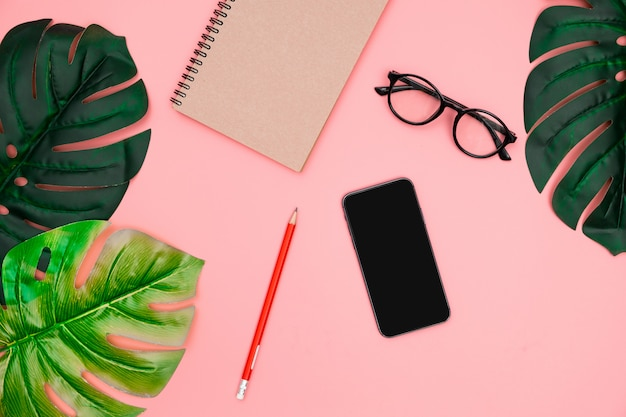 Lay plat avec smartphone, ordinateur portable, palmier tropical laisse monstera sur fond rose. Photo Premium