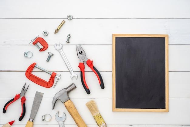 Lay plat de tableau espace vide avec des outils pratiques de construction sur fond en bois. Photo Premium