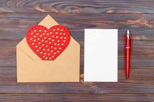 Lay plat. vue de dessus. lettre d'amour pour la saint valentin. carte postale faite à la main avec la figure en forme de coeur rouge. concept de la saint-valentin avec fond Photo Premium