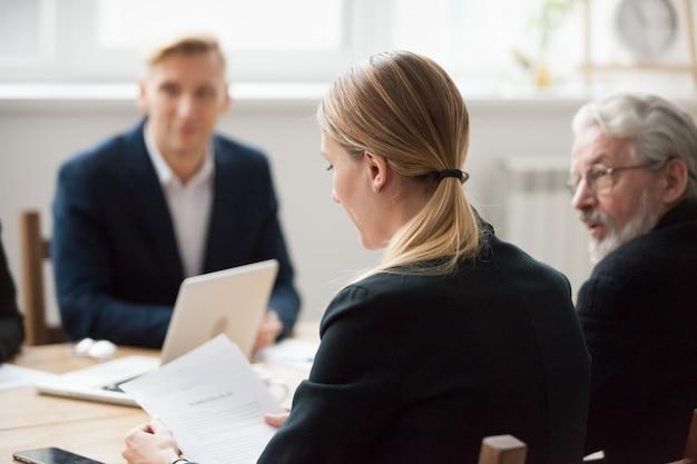 Lecture ciblée d'une femme d'affaires sérieuse lors d'une réunion de groupe ou de négociations Photo gratuit