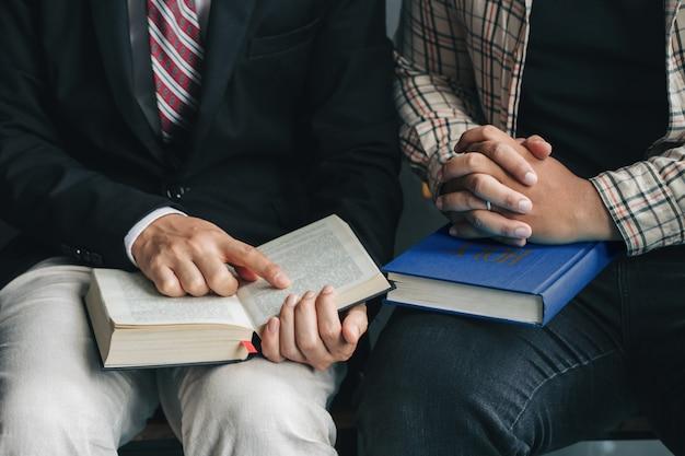 Lectures du dimanche, deux hommes lisant et étudiant la bible ensemble à la maison ou à l'école du dimanche à l'église avec la lumière d'une fenêtre Photo Premium