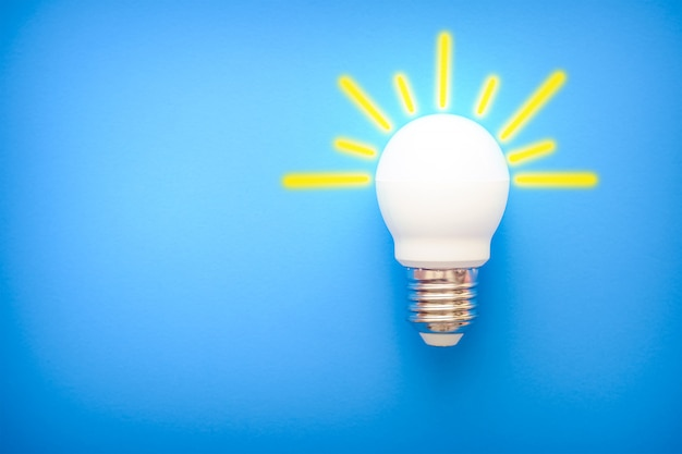 Led ampoule à rayons jaunes sur fond bleu Photo Premium