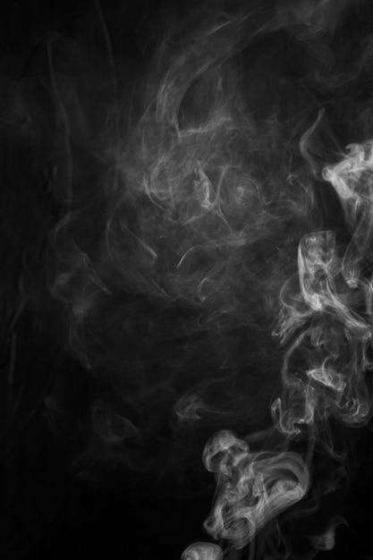Légers fragments de fumée sur fond noir Photo gratuit