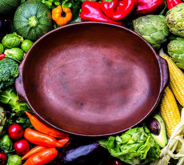 Légumes Biologiques Frais Autour D'un Pot En Argile Vide Photo Premium