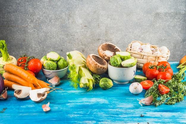 Légumes biologiques frais sur un plateau biologique bleu Photo gratuit