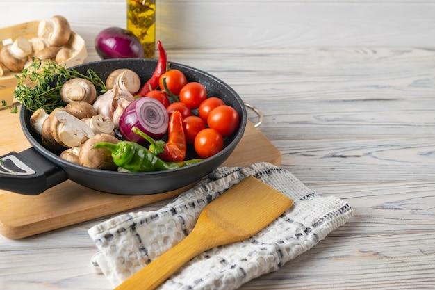 Légumes biologiques frais, tomates, champignons, poivrons et thym dans une poêle à frire Photo Premium