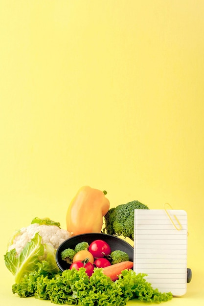 Légumes et cahier avec espace copie sur fond jaune Photo Premium