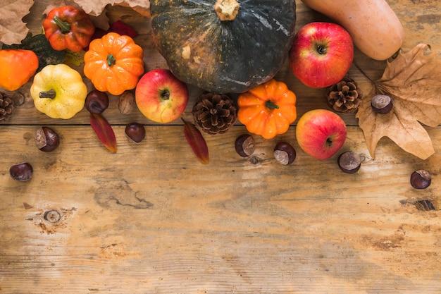 Légumes et feuilles sèches sur planche de bois Photo gratuit