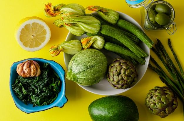 Légumes frais biologiques et épinards cuits dans un bol sur fond jaune Photo Premium