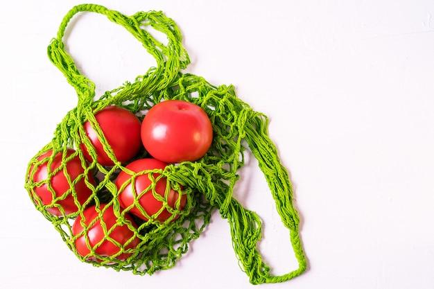 Légumes frais dans un sac à bandoulière éco réutilisable sans déchets avec une orientation horizontale et blanche. Photo Premium