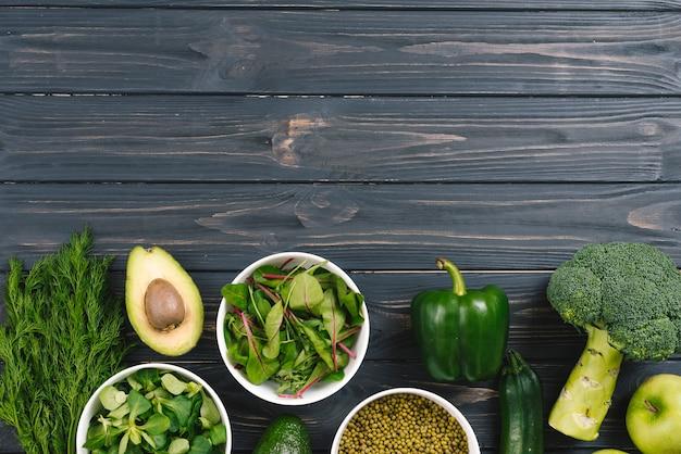 Légumes frais verts sur un bureau en bois noir Photo gratuit