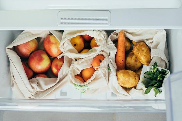Légumes et fruits frais dans des sacs en coton écologique au réfrigérateur Photo Premium