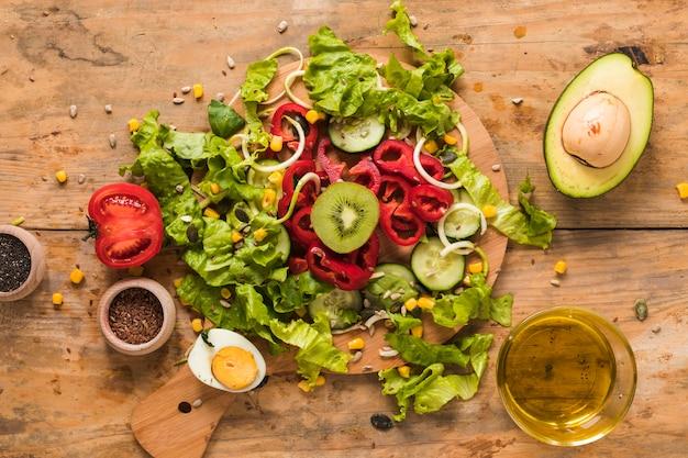 Légumes et fruits hachés sur une planche à découper avec les ingrédients; œuf à la coque et huile sur fond en bois Photo gratuit