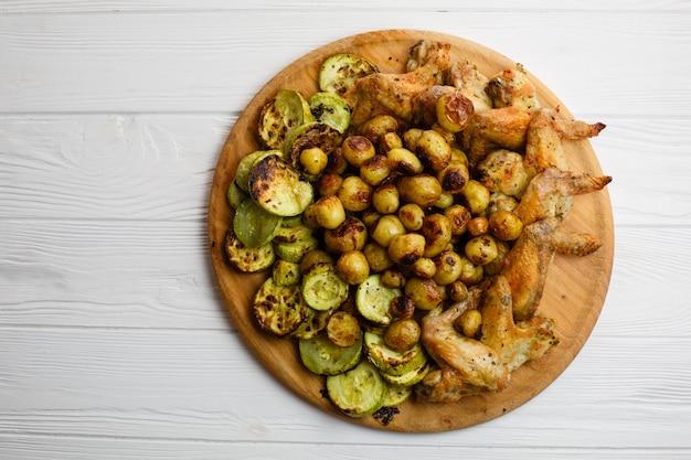 Légumes grillés et ailes de poulet sur la plaque de bois. espace libre. Photo Premium