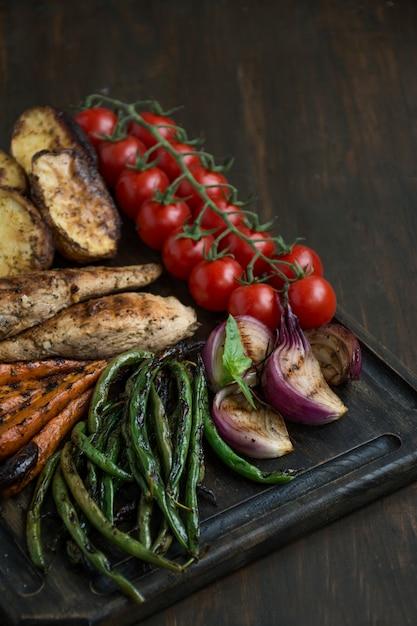 Légumes grillés sur une planche à découper sur un bois sombre. Photo Premium