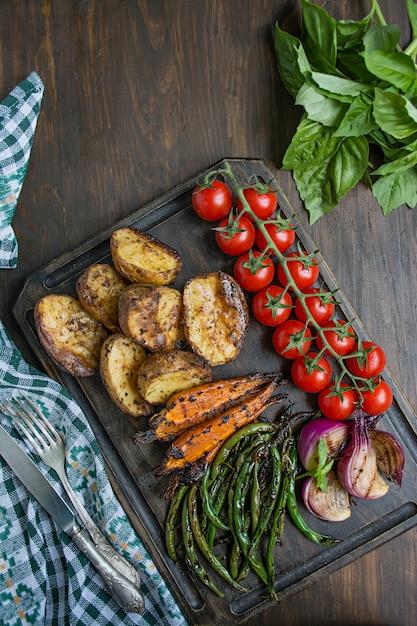 Légumes grillés sur une planche à découper sur un fond en bois foncé Photo Premium