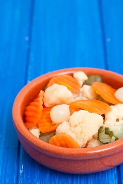 Légumes Marinés Dans Un Plat En Céramique Sur Une Surface En Bois Photo Premium
